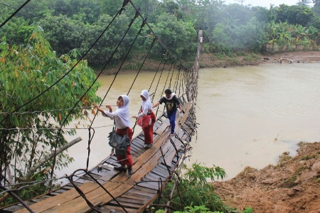 Indonesian students crossing damaged bridge